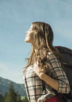 Austria, Tyrol, Tannheimer Tal, young woman on hiking trip enjoying sunshine - UUF002418