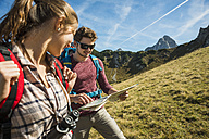 Austria, Tyrol, Tannheimer Tal, young hikers looking at map - UUF002424