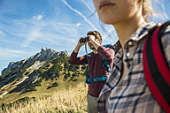 Austria, Tyrol, Tannheimer Tal, young man on hiking trip looking through binocular - UUF002436