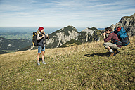 Austria, Tyrol, Tannheimer Tal, young man taking picture of girlfriend on alpine meadow - UUF002452