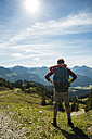 Austria, Tyrol, Tannheimer Tal, young man in mountains looking at view - UUF002460
