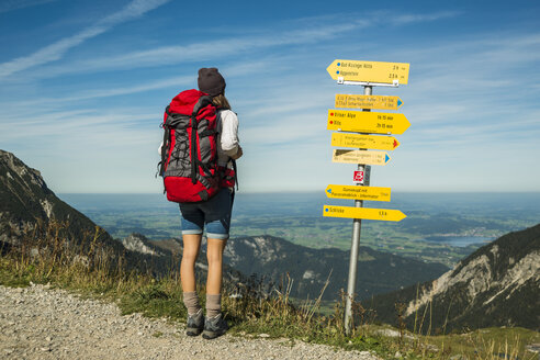 Austria, Tyrol, Tannheimer Tal, young woman on hiking trip at signpost - UUF002461
