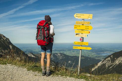 Austria, Tyrol, Tannheimer Tal, young woman on hiking trip at signpost - UUF002461