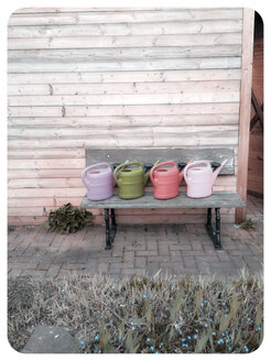 Watering cans on garden bench - EVGF000984