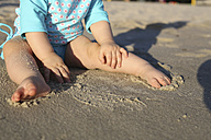 Baby girl playing on sandy beach - SHKF000052