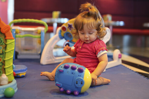 Baby girl playing with toys in a playroom of cruise liner - SHKF000082
