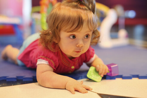 Baby girl playing with toys in a playroom of cruise liner - SHKF000084