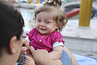 Portrait of smiling baby girl sitting on mother's lap - SHKF000089