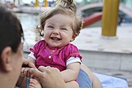 Portrait of laughing baby girl sitting on mother's lap - SHKF000090