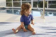 Baby girl sitting on a towel in front of swimming pool - SHKF000057