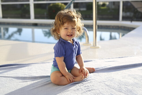 Portrait of baby girl sitting on a towel in front of swimming pool - SHKF000059