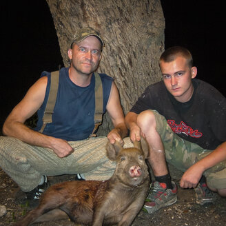 Father and son presenting young killed feral hog - ABAF001556