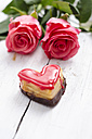 Heart shaped sponge cake and two roses on white wood - ODF000848