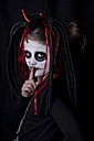 Girl with finger on her mouth masquerade as devil in front of black background - YFF000255