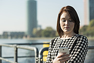 Germany, Frankfurt, young businesswoman by the riverside with cell phone - UUF002490