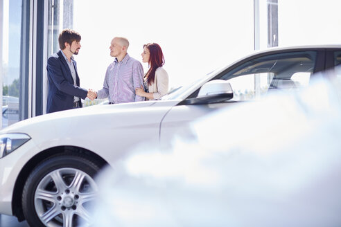 Car dealer with couple in showroom - ZEF002024