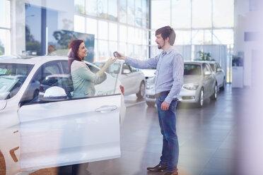 Car dealer giving key to client - ZEF002026