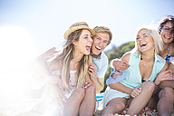 Friends socializing with laughter on the beach - ZEF002378