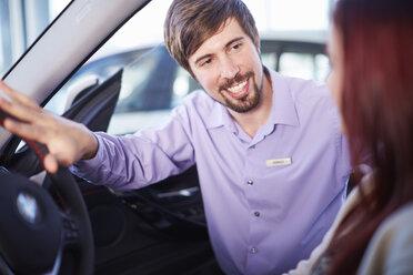 Car dealer talking to client inside car - ZEF002037