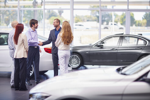 Car dealer meeting with clients in showroom - ZEF002039