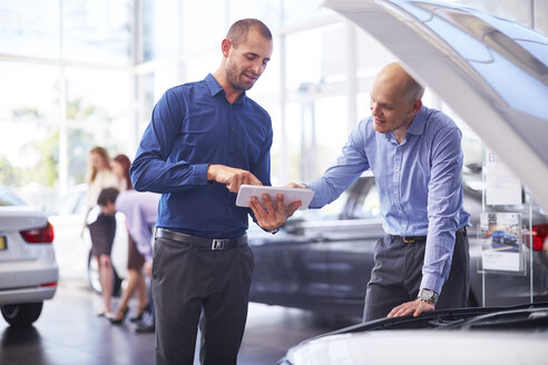 Two men at car dealer with digital tablet - ZEF002054