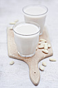 Two glasses of homemade almond milk and peeled almonds on wooden board - CZF000182