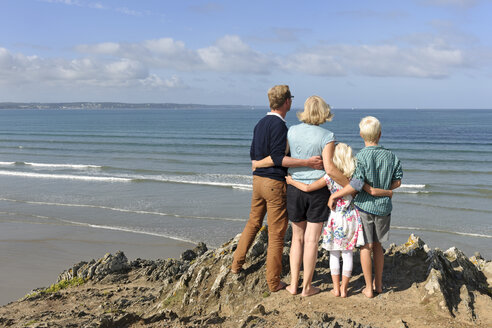 France, Bretagne, Finistere, family with two children looking together at Atlantic - LAF001177