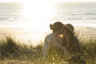 Young couple kissing at beach dunes in front of Atlantic - LAF001179