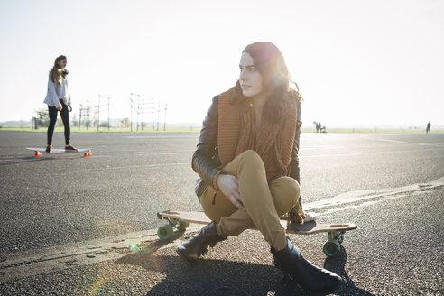 Germany, Berlin, Tempelhof Field, young woman sitting on her longboard on runway - FX000091