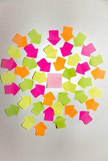Coloured arrow shaped adhesive notes and a square one on white wall - SARF000988