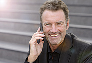 Portrait of smiling businessman sitting on steps telephoning with smartphone - GUFF000040