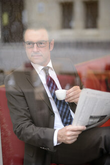 Businessman sitting in a cafe with newspaper watching something - GUFF000047