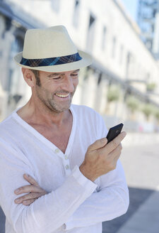Portrait of smiling mature man with stubble and summer hat using smartphone - GUFF000051