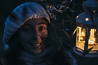 Italy, Grosseto, smiling girl with lighted Christmas lantern by night - BEBF000013