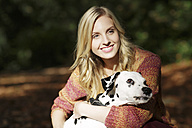Portrait of smiling blond woman with Dalmatian - GDF000541
