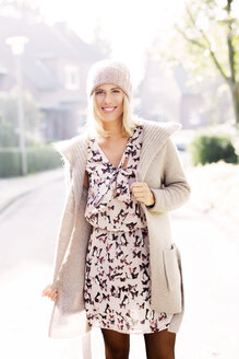 Portrait of smiling blond woman wearing patterned dress, cardigan and wool cap - GDF000546
