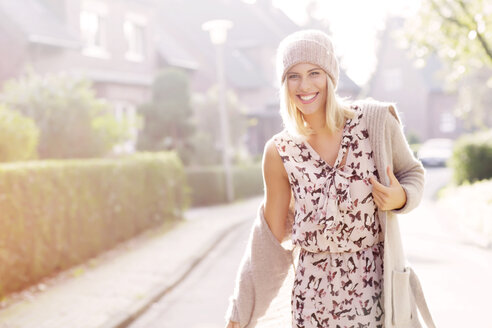 Portrait of smiling blond woman wearing patterned dress, cardigan and wool cap - GDF000550