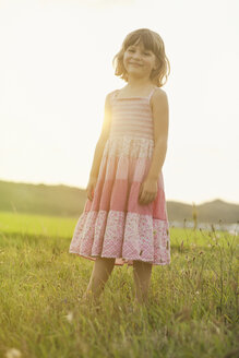 Portrait of little girl wearing summer dress standing on a meadow in backlight - MVC000136