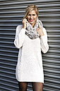 Smiling blond woman wearing knit dress and comforter standing in front of roller shutter - GDF000564