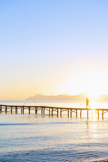 Spain, Balearic Islands, Majorca, man jogging on a jetty at sunrise - MSF004347