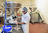 Woman working at sausage production in a butchery - LYF000333