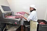Man putting cuts of meat in pickling machine in a butchery - LYF000338