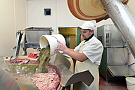 Man pouring spices into silent cutter in a butchery - LYF000344