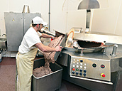 Man taking sausage meat out of silent cutter in a butchery - LYF000345