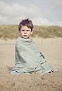 Little boy sitting on the beach warming up in a towel - MVC000137