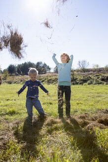 Two children throwing straw up in the air - OJF000059
