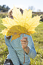 Girl hiding behind autumn leaf - OJF000062