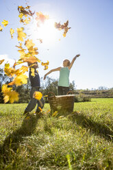 Two children throwing autumn leaves up in the air - OJF000071