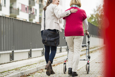 Adult granddaughter assisting her grandmother walking with wheeled walker, back view - UUF002533