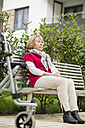 Senior woman with wheeled walker sitting on a bench - UUF002552